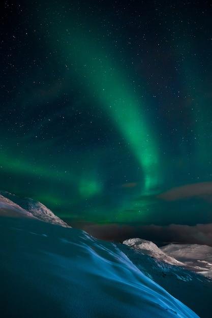 Foto vertical de uma aurora no céu acima das colinas e montanhas cobertas de neve na noruega Foto gratuita