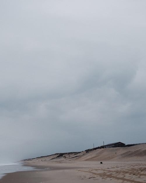 Foto vertical de uma casa solitária na praia sob um céu nublado Foto gratuita