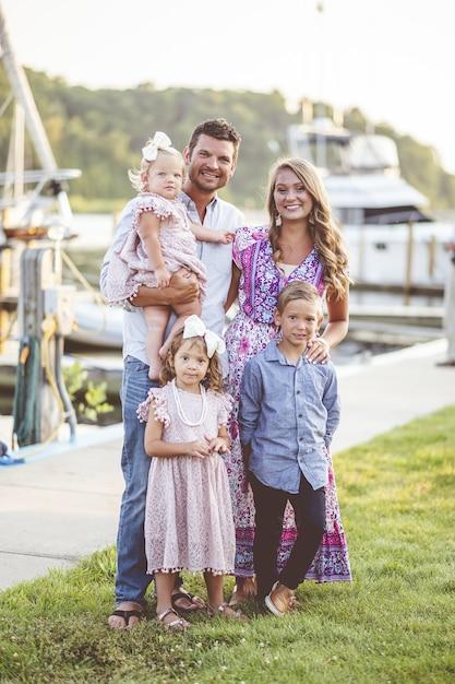 Foto vertical de uma família feliz em pé na grama perto do porto Foto gratuita