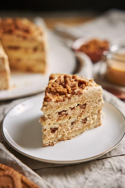 Foto vertical de uma fatia de bolo de biscoito de lótus delicioso com caramelo com biscoitos na mesa Foto gratuita