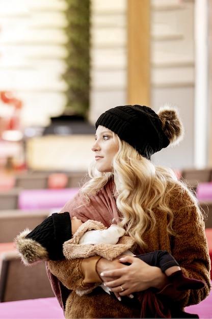 Foto vertical de uma jovem loira segurando seu bebê olhando para o lado Foto gratuita