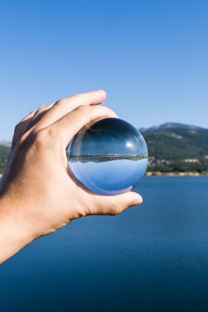 Foto vertical de uma mão de uma pessoa segurando uma bola de cristal que reflete a paisagem de um lago com montanhas em um reservatório de água em navacerrada na serra em madri Foto Premium