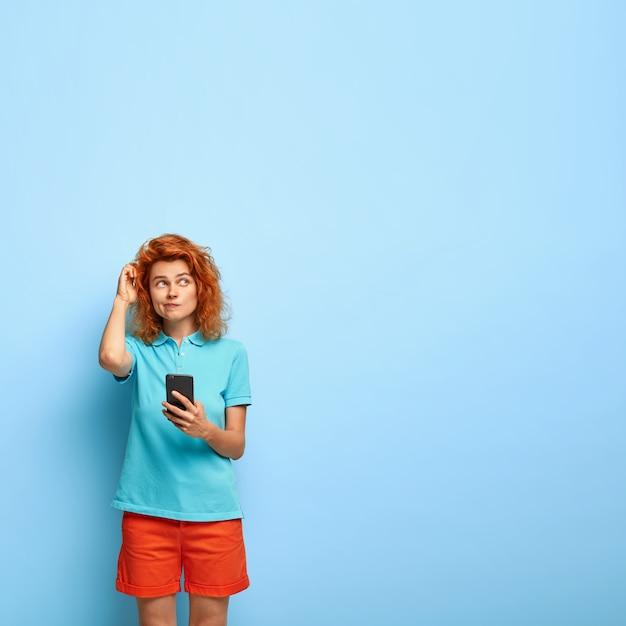 Foto vertical de uma menina ruiva pensativa coçando a cabeça e olhando com espanto Foto gratuita