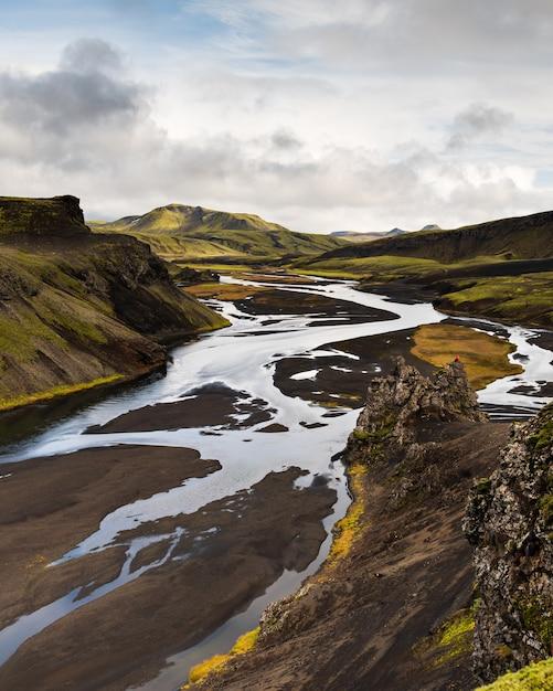 Foto vertical de uma montanha na região das terras altas da islândia com um céu nublado Foto gratuita