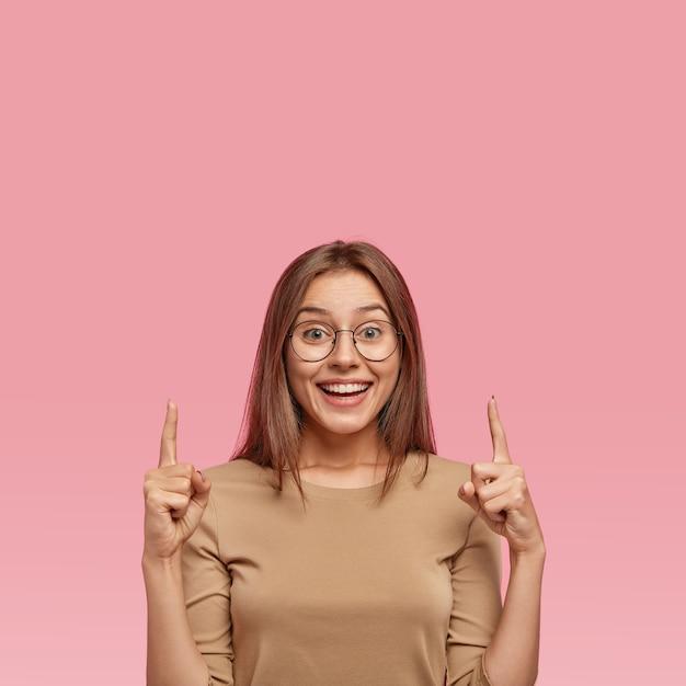 Foto vertical de uma mulher feliz de cabelos escuros com um sorriso cheio de dentes Foto gratuita