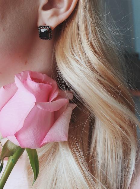 Foto vertical de uma mulher loira usando um brinco com uma pérola negra segurando uma rosa Foto gratuita