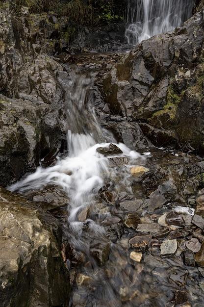 Foto vertical de uma pequena cachoeira fluindo de uma montanha íngreme Foto gratuita