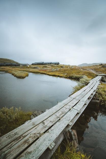 Foto vertical para uma doca de madeira sobre um lago em finse, noruega Foto gratuita