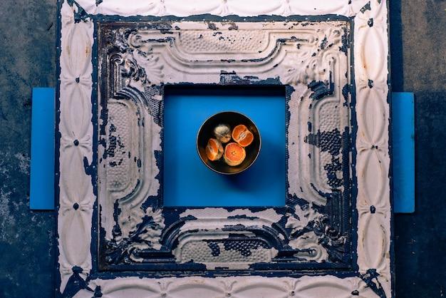 Fotografia abstrata de mandarinas banhadas em metal em uma tigela sobre uma superfície azul e madeira Foto gratuita