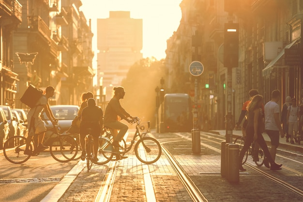 Fotografia de rua, pessoas atravessando a rua durante o pôr do sol na cidade de bordeaux, frança. estilo vintage Foto Premium