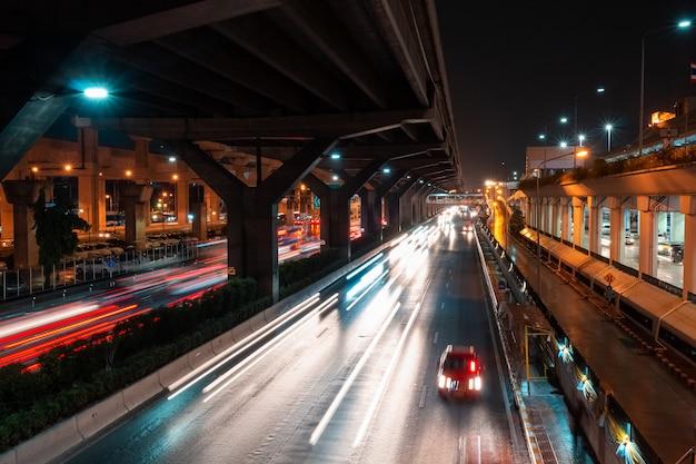 Fotografia longa da exposição que mostra o tracffic claro na estrada na cidade. Foto Premium