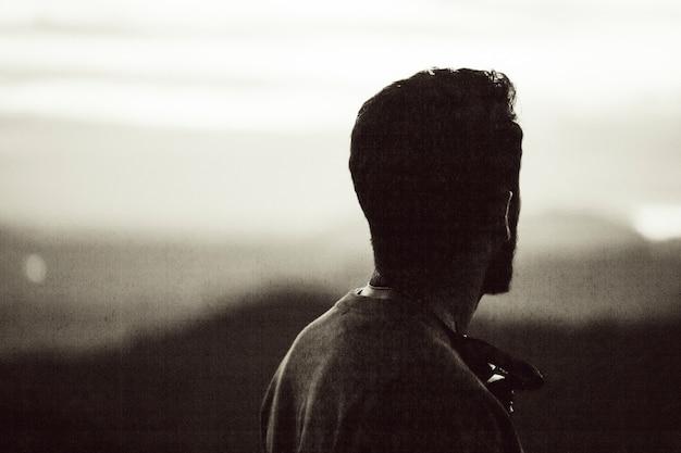 Fotografia vintage de um homem olhando para o horizonte Foto gratuita