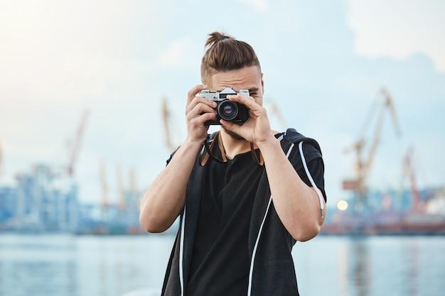 Fotógrafo com câmera vintage tirando fotos perto do mar, andando pela cidade para imaginar todos os momentos interessantes Foto gratuita