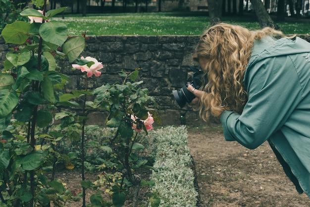 Fotógrafo da mulher da idade média que faz um tiro da foto com uma câmara digital do dslr em um parque. Foto Premium