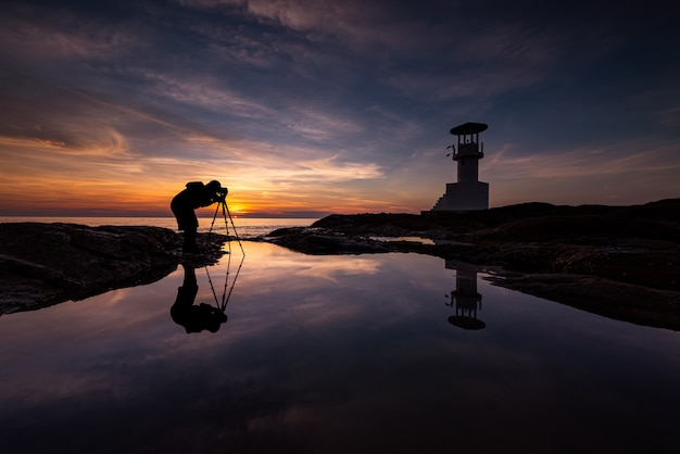 Fotógrafo da silhueta com farol Foto Premium