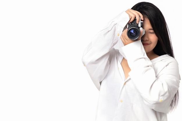 Fotógrafo de mulher trabalhando em estúdio. fotografia asiática da mulher em ação no fundo branco. menina que veste a camisa branca que mantem a câmera do vintage disponivel livre do espaço da cópia. Foto Premium