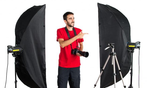 Fotógrafo em seu estúdio apontando para o lateral Foto Premium
