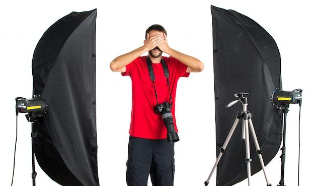 Fotógrafo em seu estúdio cobrindo os olhos Foto Premium