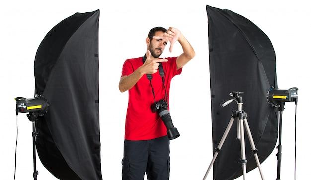 Fotógrafo em seu estúdio, concentrando-se com os dedos Foto Premium