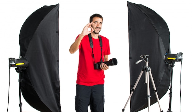 Fotógrafo em seu estúdio fazendo sinal de ok Foto Premium