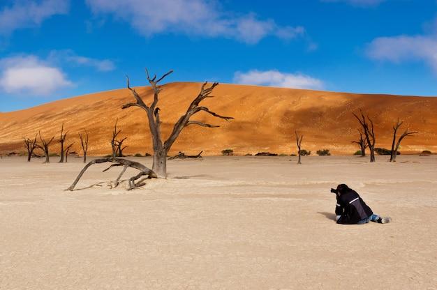 Fotógrafo fazendo imagem da paisagem de dead vlei, sossusvlei, deserto do namibe. namíbia, áfrica do sul Foto Premium