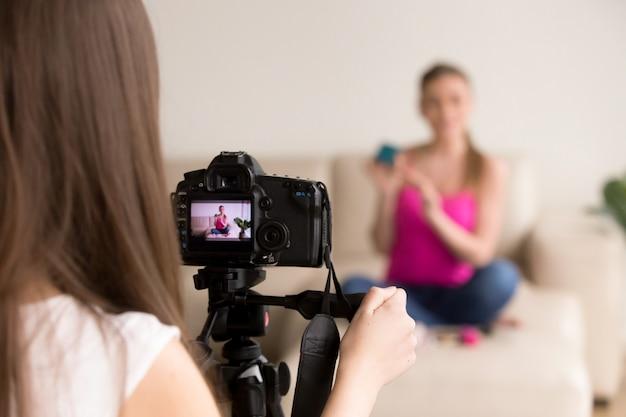 Fotógrafo fêmea que toma a foto da menina no sofá. Foto gratuita