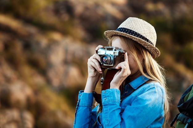 Fotógrafo feminino loiro lindo tirando foto da paisagem do canyon Foto gratuita