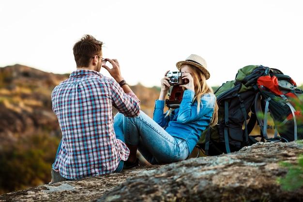 Fotógrafo feminino loiro lindo tirando foto do namorado, fundo do canyon Foto gratuita