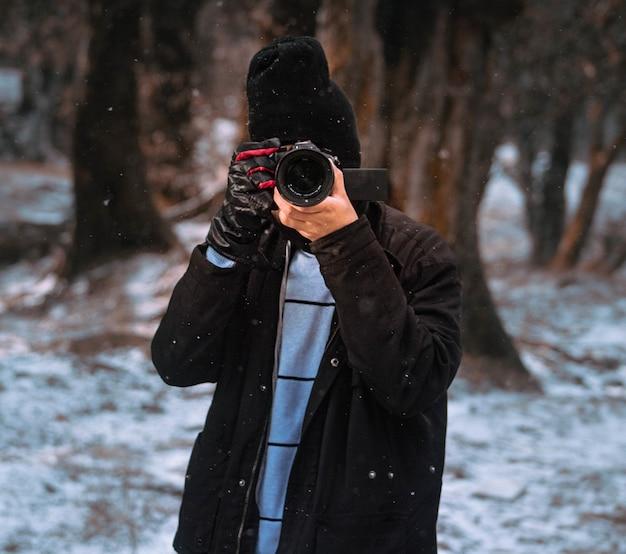 Fotógrafo masculino capturando o inverno na floresta Foto gratuita