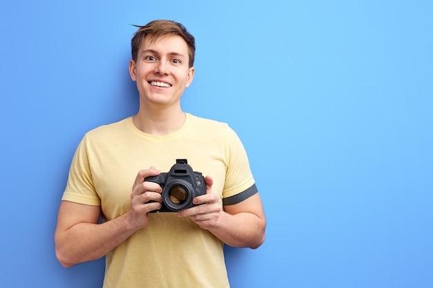 Fotógrafo masculino segurando uma câmera profissional nas mãos e sorrindo para a câmera, tirar uma foto. homem sorridente em camiseta casual isolado sobre fundo azul Foto Premium