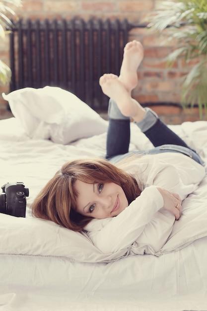 Fotógrafo mulher deitada na cama com a câmara fotográfica Foto gratuita