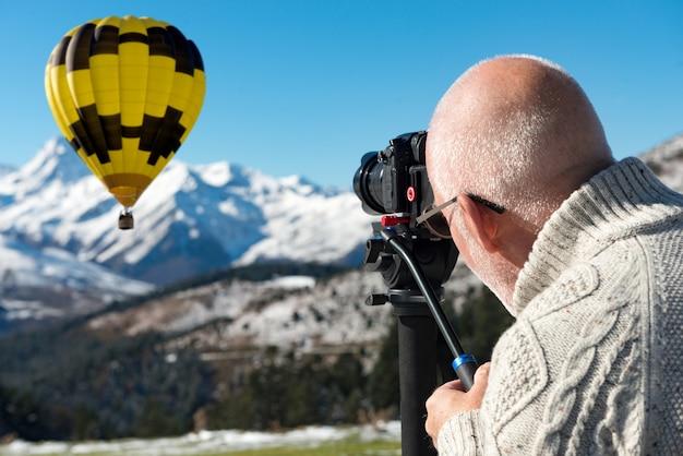 Fotógrafo no topo da montanha com balão de ar quente Foto Premium