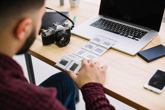Fotógrafo olhando negativos Foto gratuita