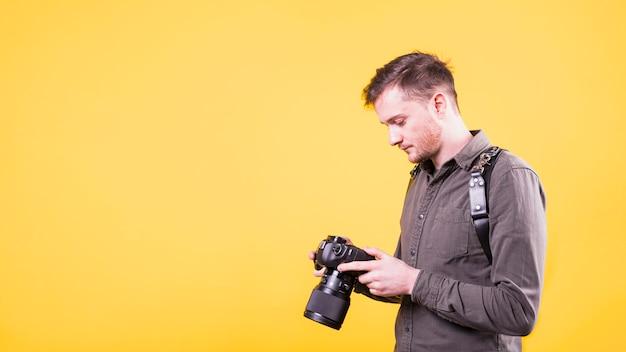 Fotógrafo, olhando para a tela da câmera Foto gratuita