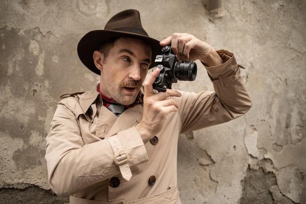 Fotógrafo paparazzo usando a câmera em uma rua da cidade Foto Premium