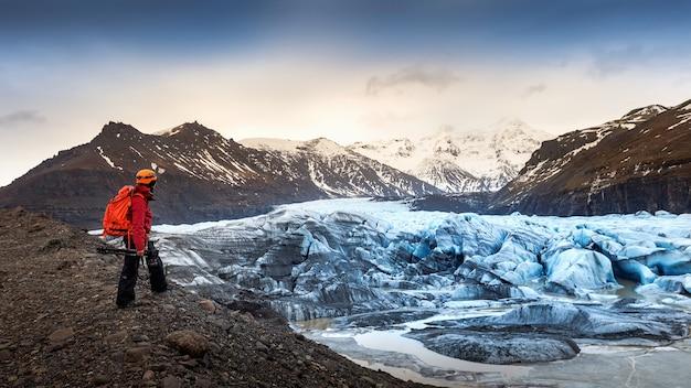 Fotógrafo profissional com câmera e tripé no inverno. fotógrafo profissional olhando para uma geleira na islândia. Foto gratuita