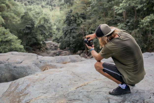 Fotógrafo tira fotos da floresta Foto gratuita