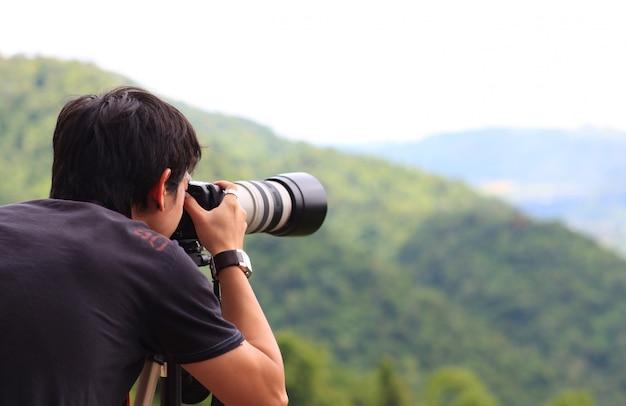 Fotógrafo tirando uma foto ao ar livre Foto gratuita