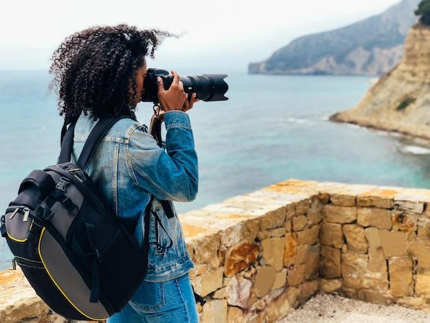 Fotógrafo tirando uma foto de uma costa do oceano Foto Premium