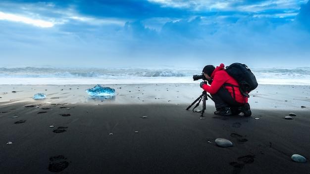 Fotógrafo tirando uma foto no gelo na islândia. Foto gratuita