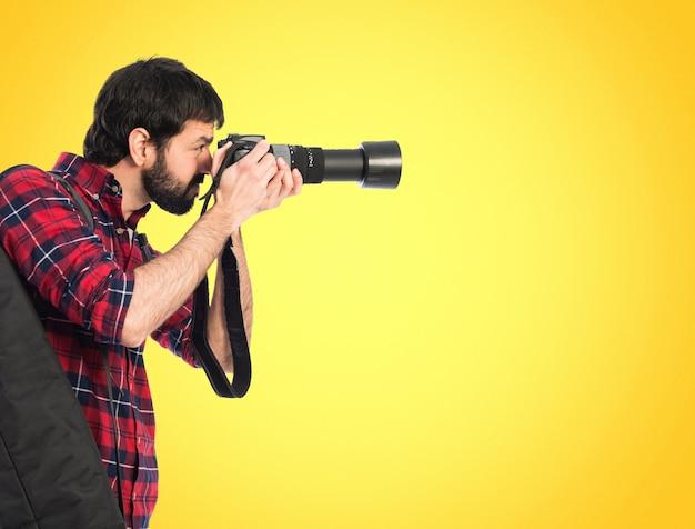 Fotógrafo tomando uma foto em fundo colorido Foto Premium