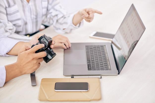 Fotógrafos de coworking com gadget na mesa Foto gratuita