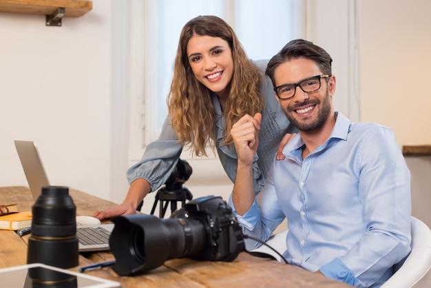 Fotógrafos profissionais com câmera e laptop trabalhando no estúdio. fotógrafo com assistente sentado no escritório e. equipe de fotógrafos trabalhando juntos. Foto Premium