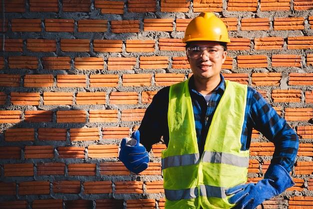 Fotos de trabalhadores da construção civil asiáticos no canteiro de obras ou fotos de trabalhadores da construção civil no canteiro de obras mon brick background Foto Premium