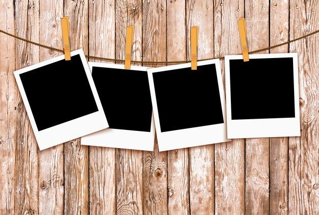Fotos na corda com prendedores de roupa em fundo de madeira Foto Premium