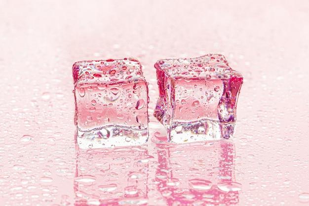 Fozen cubos de gelo no rosa molhado Foto Premium