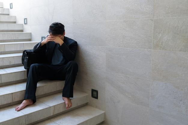 Fracasso nos negócios jovens empresários sentam-se nas escadas e suas mãos apertaram a cabeça. porque ele está tão desesperado, estressado, tristeza depois de saber as más notícias de que está desempregado. Foto Premium