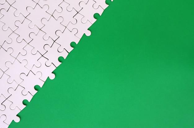 Fragmento de um quebra-cabeça branca dobrada no fundo de uma superfície de plástico verde Foto Premium