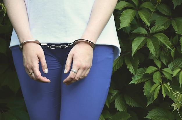 Fragmento do corpo de uma jovem criminosa com as mãos algemadas Foto Premium