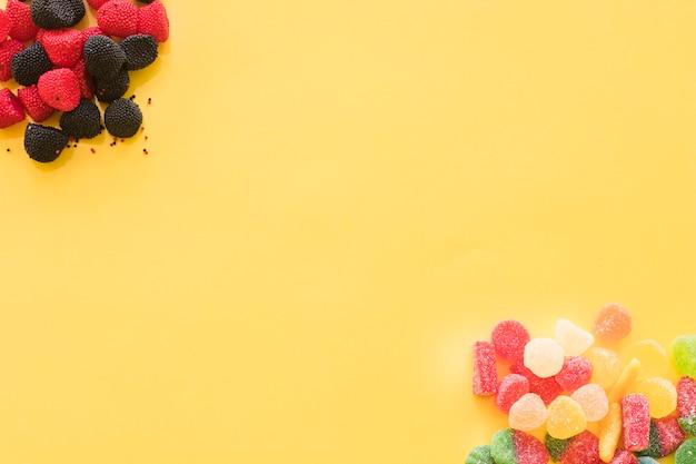 Framboesa e amora com sabor e em forma de geleia doces no canto do fundo amarelo Foto gratuita